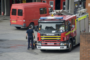 Fireman working on a fire engine parked in the courtyard of the fire station